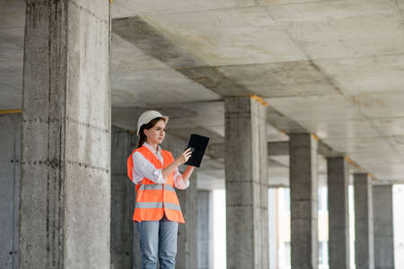 Construction concept of Engineer or Architect working at Construction Site. A woman with a tablet at a construction site. Bureau of Architecture 版權商用圖片
