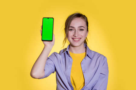 Young woman pointing at green screen on smartphone on yellow background.