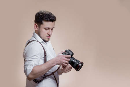 photographer with camera on brown background, successful professional male looks at photos on screen of camera. photography concept.