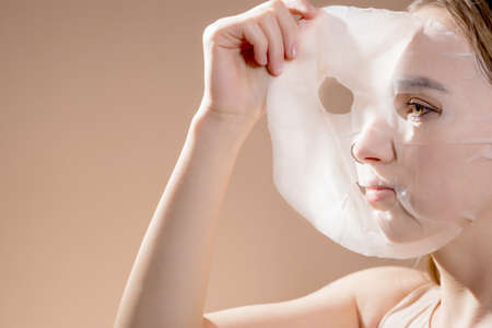 Woman apply or takes off white cosmetic fabric facial mask