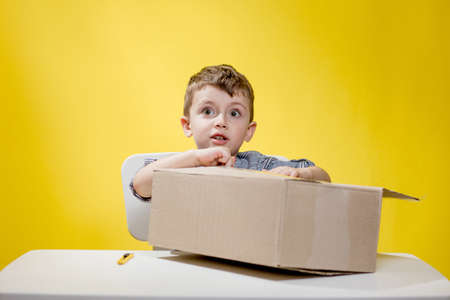 Surprised boy looking opening a box and gasping in surprise seeing the content of the box while recording an unboxing vlog.