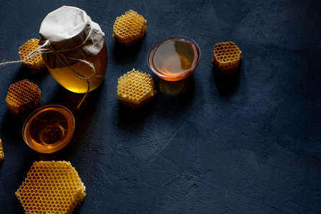 Jar of honey with honeycomb on black table, top view. space for text.