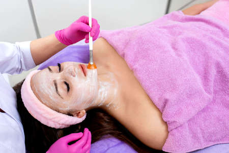 Face peeling mask, spa beauty treatment, skincare. Woman getting facial care by beautician at spa salon, side view, close-up. Anti-aging treatment. Cosmetology and professional facial skin care