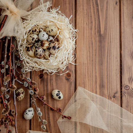 Easter quail eggs in nest and willow branch on a wooden background, copy space.