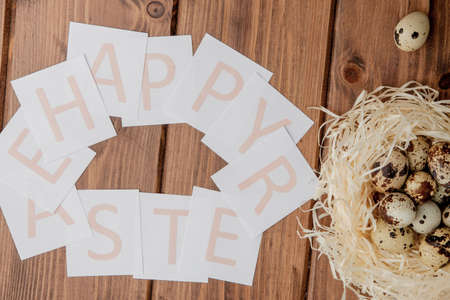 Flat lay composition of quail eggs and card with text Happy Easter on wooden table. Top view