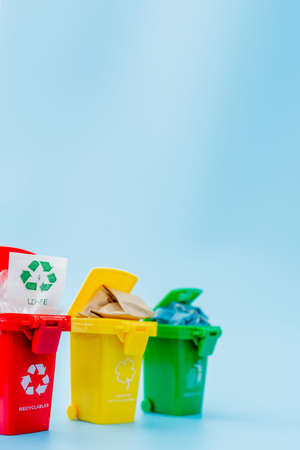 Yellow, green and red recycle bins with recycle symbol on blue background. Keep city tidy, Leaves the recycling symbol. Nature protection concept. 版權商用圖片