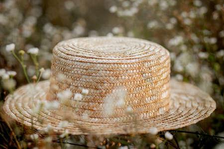 hat on wild white flowers.