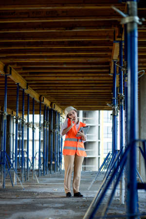 Construction concept of Engineer or Architect working at Construction Site. A woman with a tablet at a construction site. Bureau of Architecture.