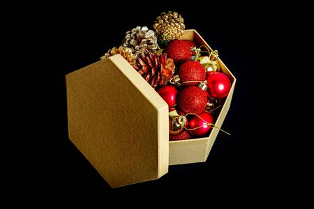 Open box with New Years toys and cones on a black background