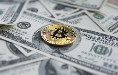 Golden Bitcoins on US dollars. Digital currency close-up. New virtual money. Crypto currency top view. Real coins of bitcoin on banknotes of one hundred dollars. Exchange. Bussiness, commercial. Фото со стока
