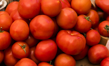 Close up of fresh organic tomatos at outdoor market. Delicious red tomatoes. Summer tray market agriculture farm full of organic vegetables It can be used as background.