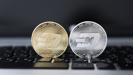 Silver and Gold Dash Cryptocurrency on laptop keyboard. Virtual money. Bussiness, commercial. Digital money and virtual crypto currency concept. Investment. Bussiness, commercial. Profit from mining.