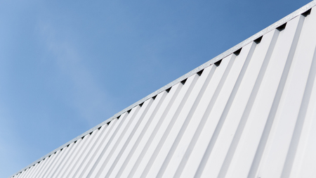 Metal white sheet for industrial building and construction on blue sky background. Roof sheet metal or corrugated roofs of factory building or warehouse.
