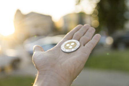 Golden silver Ripple coin in hand on a blurred sunset background. Hand holding a crypto currency virtual money. Bussiness, commercial, exchange, digital money.