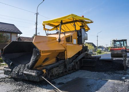 道路工事や修理工事中にアスファルト舗装機を操作する労働者。舗装フィニッシャー、アスファルトフィニッシャー、または舗装機でアスファルトの層を配置。再舗装