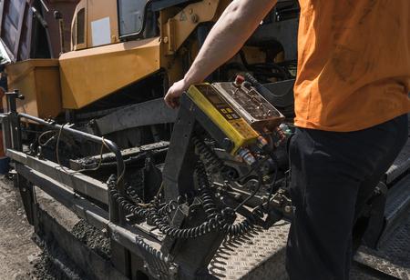 道路工事や修理工事中にアスファルト舗装機を操作する労働者。舗装フィニッシャー、アスファルトフィニッシャー、または舗装機でアスファルトの層を配置。再舗装 写真素材