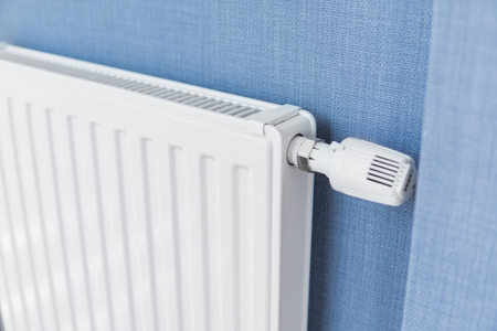 White radiator in an apartment with a blue walls.