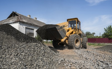 Yellow loader moving with uploaded bucket with stone gravel during road construction works. The stones for the road. Unloading stone.