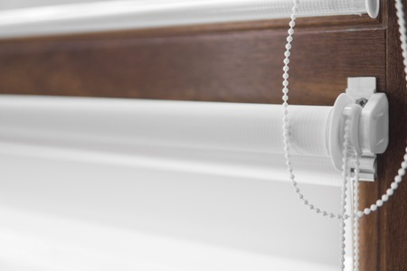 Details of white fabric roller blinds on the plastic window with wood texture in the living room. Archivio Fotografico