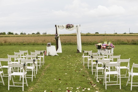 Beautiful wedding ceremony on a field with white chairs. Place for wedding ceremony with wedding arch decorated with cloth, flowers and white chairs on each side of archway outdoors. 스톡 콘텐츠