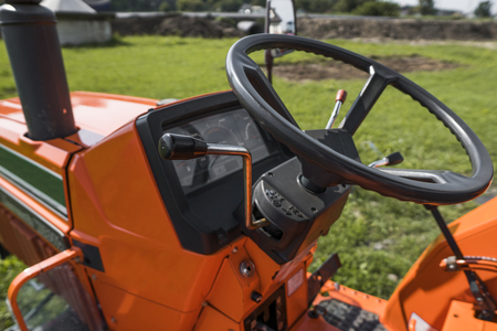 A small mini orange tractor stands on a farm yard on green grass and waits for work to begin.