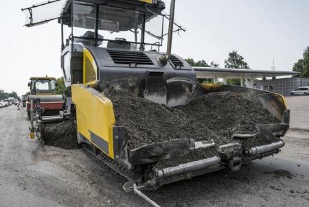 Asphalt paver machine during road construction and repairing works. A paver finisher, asphalt finisher or paving machine placing a layer of asphalt. Repaving.