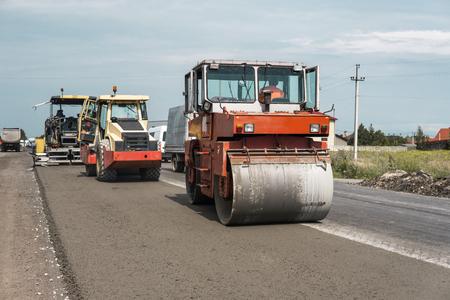 アスファルト舗装のオレンジ重振動ローラーコンパクターは、道路の修理のために働きます。新しい道路建設現場で作業。修理。