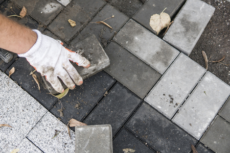 Hands of a builder in his orange gloved hands with a hammer fitting laying new exterior paving stones carefully placing one in position on a leveled and raked soil base. Sand foundation. Building. Banque d'images