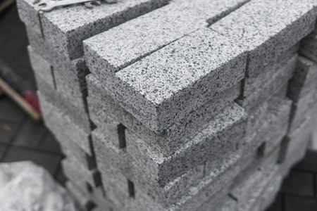 pavement cobblestone in the stack on the street. Concrete or granite gray square pavement slabs for sidewalk construction. Industry manufacturing or building concept. Construction material. Standard-Bild
