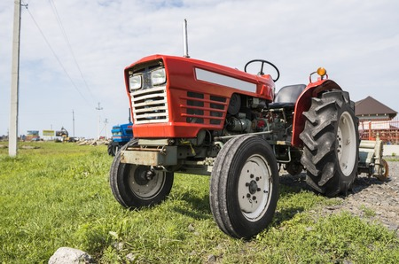 A small mini red tractor stands on a farm yard on green grass and waits for work to begin.