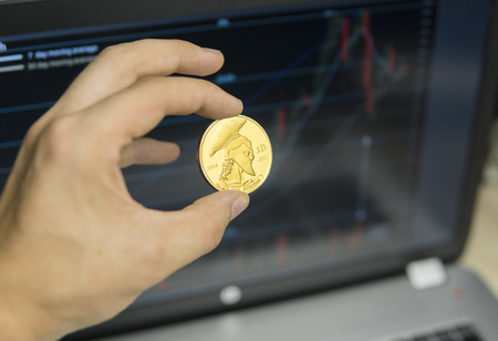 Male businessman hand holding titan bitcoin on a background of growth graph on a screen of laptop. Virtual money and Financial growth concept on chart background. Trading Mining of bitcoins. Stock fotó