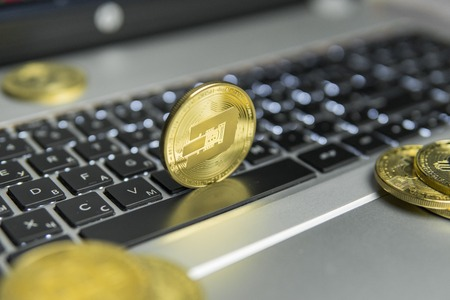 Golden Dash coin with gold coins lying around on a black keyboard of silver laptop and diagram chart graph on a screen as a background. Mining of dash online bussiness. Trading