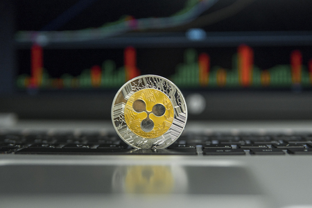 Golden and Silver Ripple coin on a black keyboard of silver laptop and diagram chart graph on a screen as a background. Virtual cryptocurrency concept. Mining of ripples online bussiness. Trading