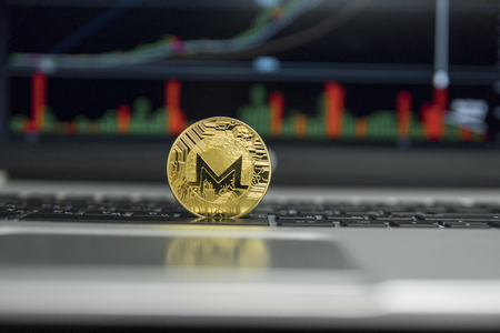 Golden coin of Monero on a black keyboard of silver laptop and diagram chart graph on a screen as a background. Cryptocurrency concept. Mining of ethereums online bussiness. Trading Stock Photo