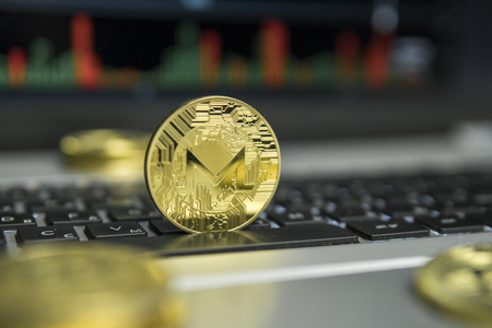 Golden Monero coin with gold coins lying around on a black keyboard of silver laptop and diagram chart graph on a screen as a background. Mining of Moneros online bussiness. Trading