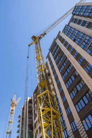 Construction of a high-rise building with a crane. Building construction using formwork. Cranes and buildings against the blue sky.