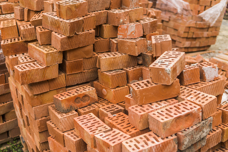 Stack of red brick for construction. Common quality building bricks stacked ready for use.