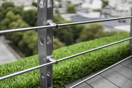 Details of fence made of stainless steel profile with an artificial raffa on the background.