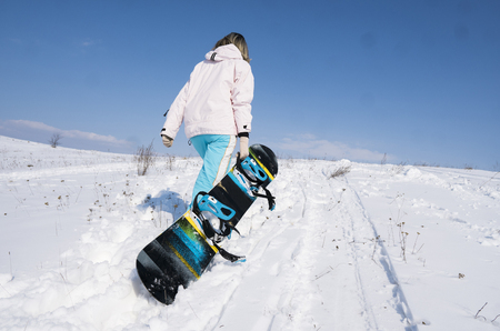 Girl snowboarder with a snowboard on a white snow. Stok Fotoğraf