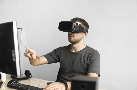 Young man wearing virtual reality goggles headset and sitting in the office against computer. Connection, technology, new generation. Man trying to touch objects or control VR with a hand. 免版税图像