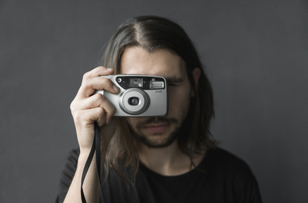 Handsome young bearded man with a long hair and in a black shirt holding vintage old-fashioned film camera on a black background and looking in camera viewfinder.