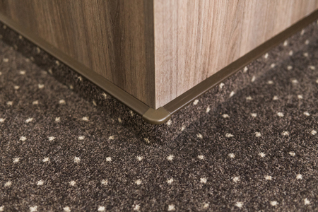 Brown carpet floor with a white dots with a carpet baseboard on a wood-based panels wall. Stock Photo