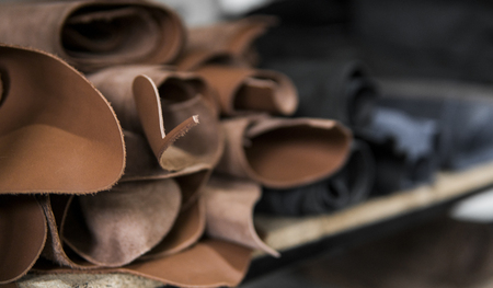 Different pieces of leather in a rolls. The pieces of the colored leathers. Rolls of natural brown red leather. Raw materials for manufacture of bags, shoes, clothing and accessories. Фото со стока