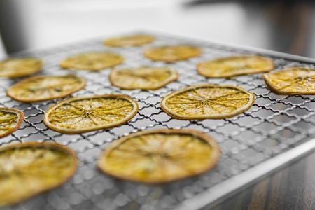 Candied orange slices on grid for drying. Dried fruits which can be used as a decoration to the meal or cocktails. Healthy vegetarian food rich on a vitamins and microelements.