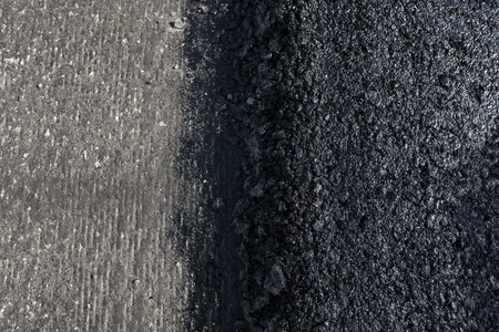 Freshly laid black bitumen asphalt with a high edge to the gravel showing the structure. Laying a new asphalt on the roads. Construction of the road. 写真素材