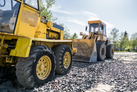 Yellow loader with empty bucket stands on a stone gravel during road construction works. The stones for the road. Unloading stone.