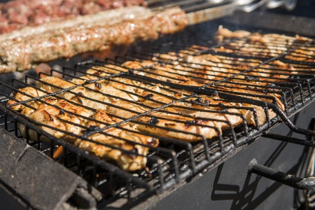 Assorted delicious grilled meat over the coals on barbecue.