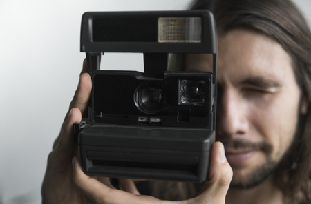 Handsome young bearded man with a long hair and in a black shirt holding vintage old-fashioned film camera on a white background and looking in camera viewfinder. Stock Photo