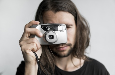 Handsome young bearded man with a long hair and in a black shirt holding vintage old-fashioned film camera on a white background and looking in camera viewfinder. Standard-Bild