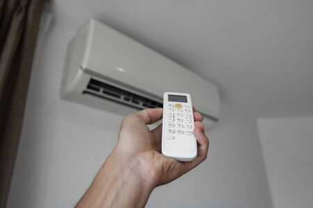 Mans hand using remote controler. Hand holding rc and adjusting temperature of air conditioner mounted on a white wall. Indooor comfort temperature. Health concepts and energy savings. Stockfoto